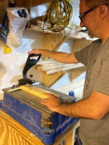 A man uses the Kreg Foreman Pocket-Hole Machine to drill pocket holes